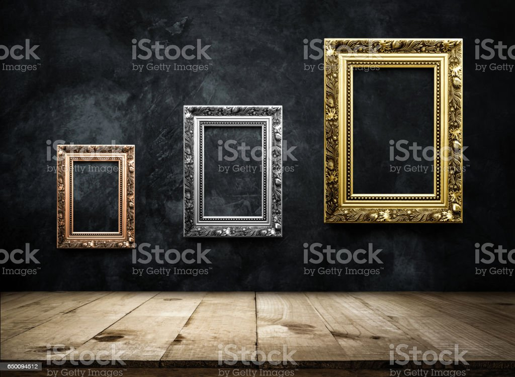 Antique picture Frame copper, silver, gold on dark grunge wall with Wooden table top, Empty ready for product display or montage. stock photo