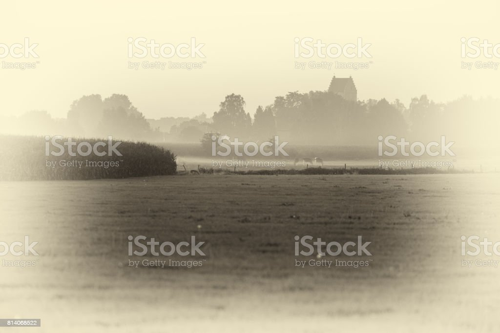 Antique plate photography of ancient churchtower of dutch rural village over misty corn field. stock photo