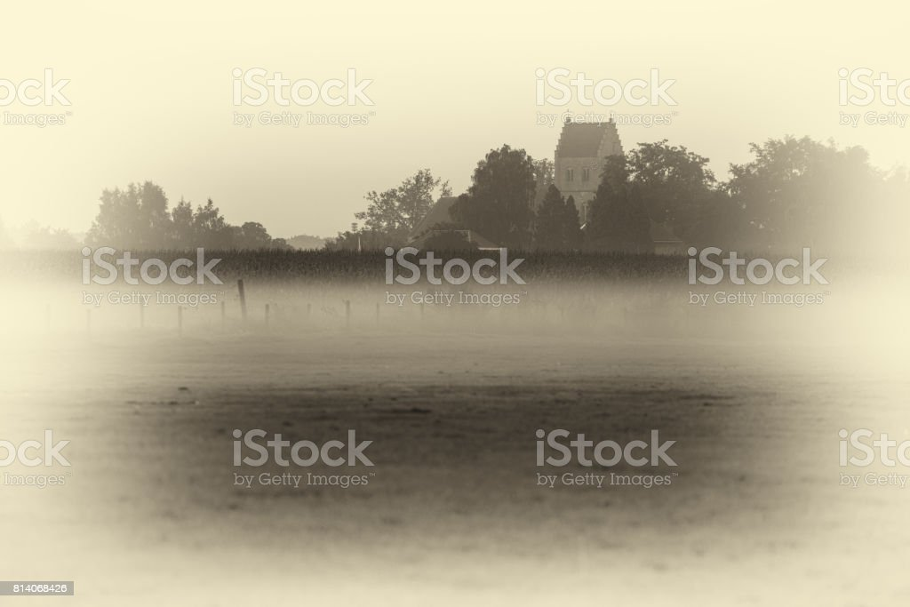 Antique plate photography of ancient churchtower over corn field in morning fog. Geesteren. Gelderland. The Netherlands. stock photo