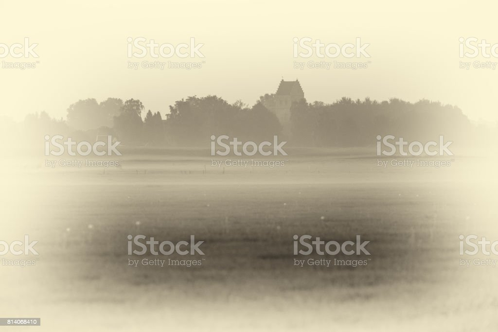 Antique plate photography of old rural dutch village with churchtower in mist. stock photo