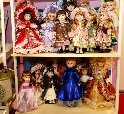 Antique porcelain dolls collection standing on shelves
