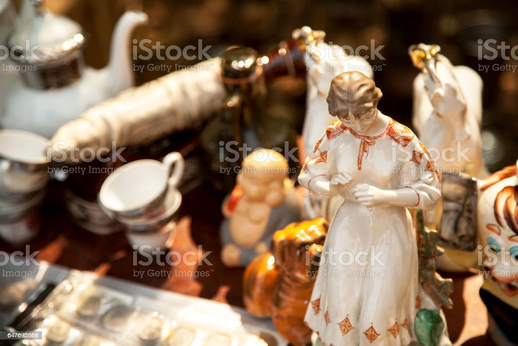 Antique porcelain woman figurine and crockery at the flea market stock photo
