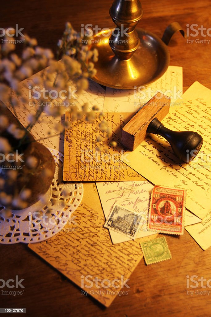 Antique postcards and stamp on a wooden desk stock photo