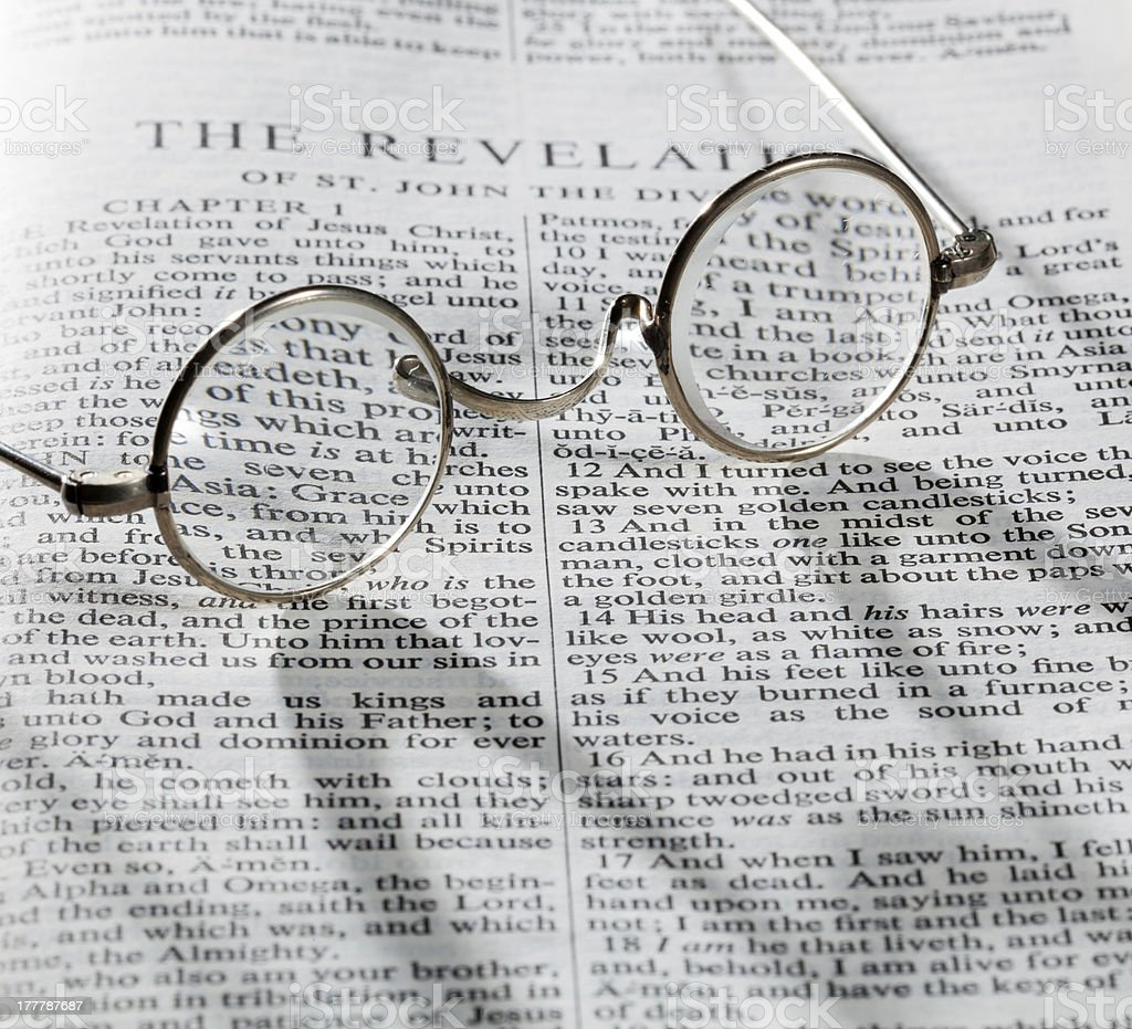 Antique reading glasses on page of bible stock photo