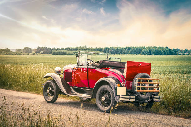 Antique red car on a road in a countryside landscape stock photo