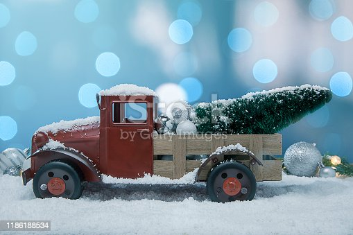 This is a photograph of antique pickup truck with a christmas tree in the back with blue and white and Silver Christmas ornaments shot in the snow surrounded by glowing Christmas lights surrounded by evergreen palm tree branches. There are no people in the photograph