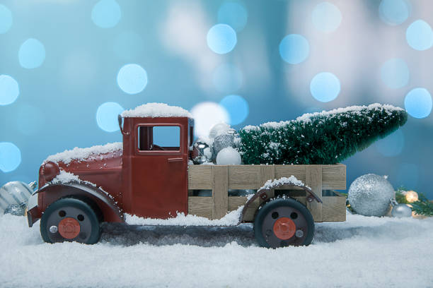 Antique Red pickup Truck in the snow with christmas tree in the back stock photo