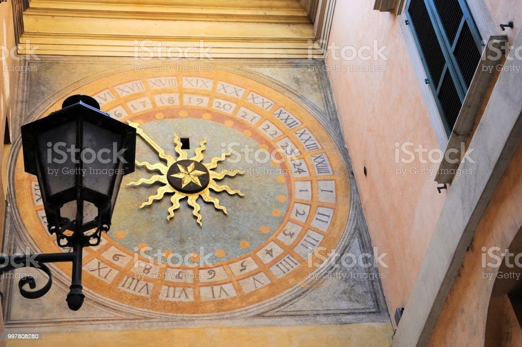 Antique renaissance clock in an alley in the city with old street lamp. Brescia, Italy. - foto stock