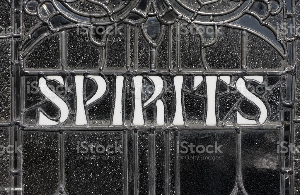 Leaded pub window with old stained glass spirits sign stock photo