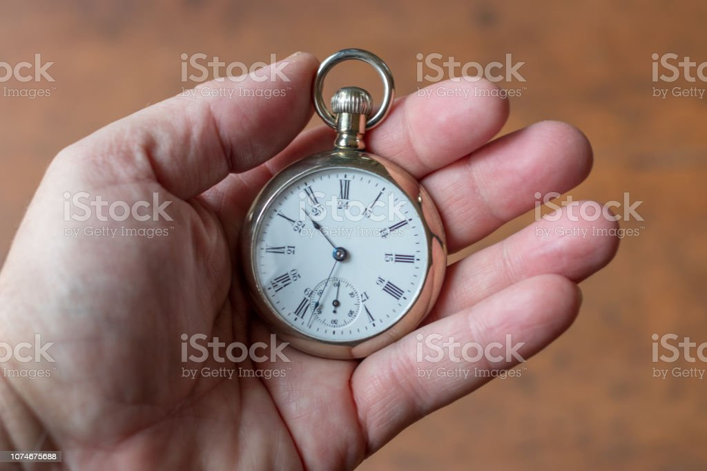 Antique silver pocket watch in a man's hand. stock photo