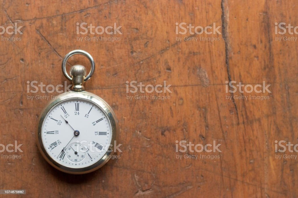 Antique silver pocket watch on a brown wooden background. stock photo