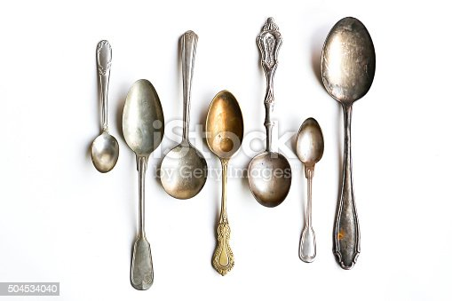 Antique silver spoons isolated on white background.