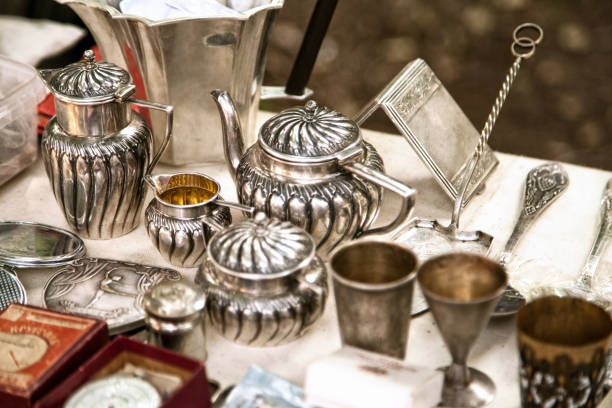 Antique silver teapots, creamer and other utensils at a flea market stock photo