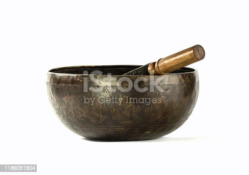 Studio shot of an antique singing bowl (ring gong, resting or standing bell) made of brass with a wooden striker. This is a typically music instrument used Himalayan regions in Tibet and Ladakh.