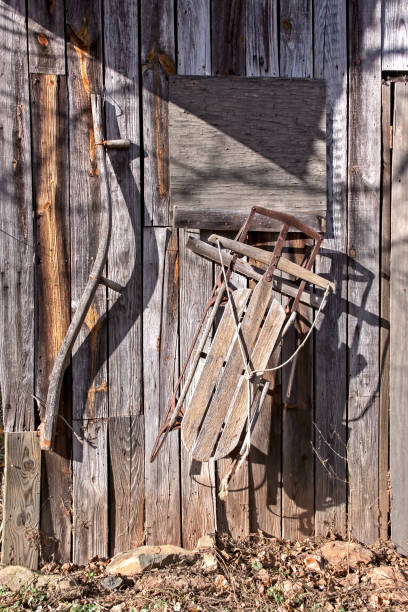 Antique Snow Sled on Old Wooden Barn stock photo