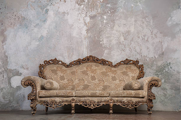antique sofa against old stucco background - baroque stock photos and pictures