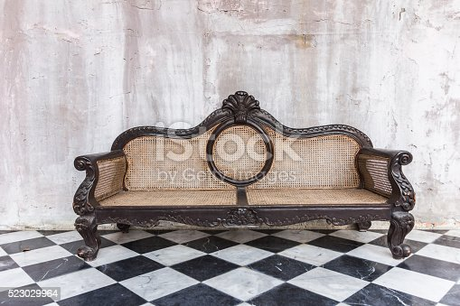 istock Antique sofa against old stucco background 523029964