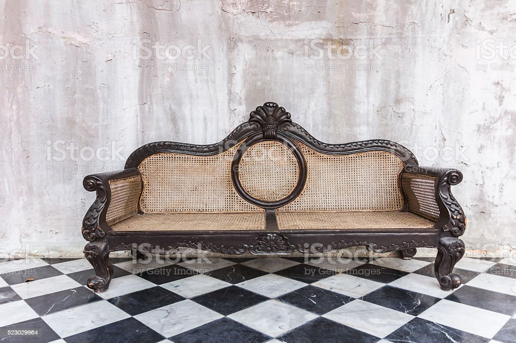 Antique sofa against old stucco background stock photo