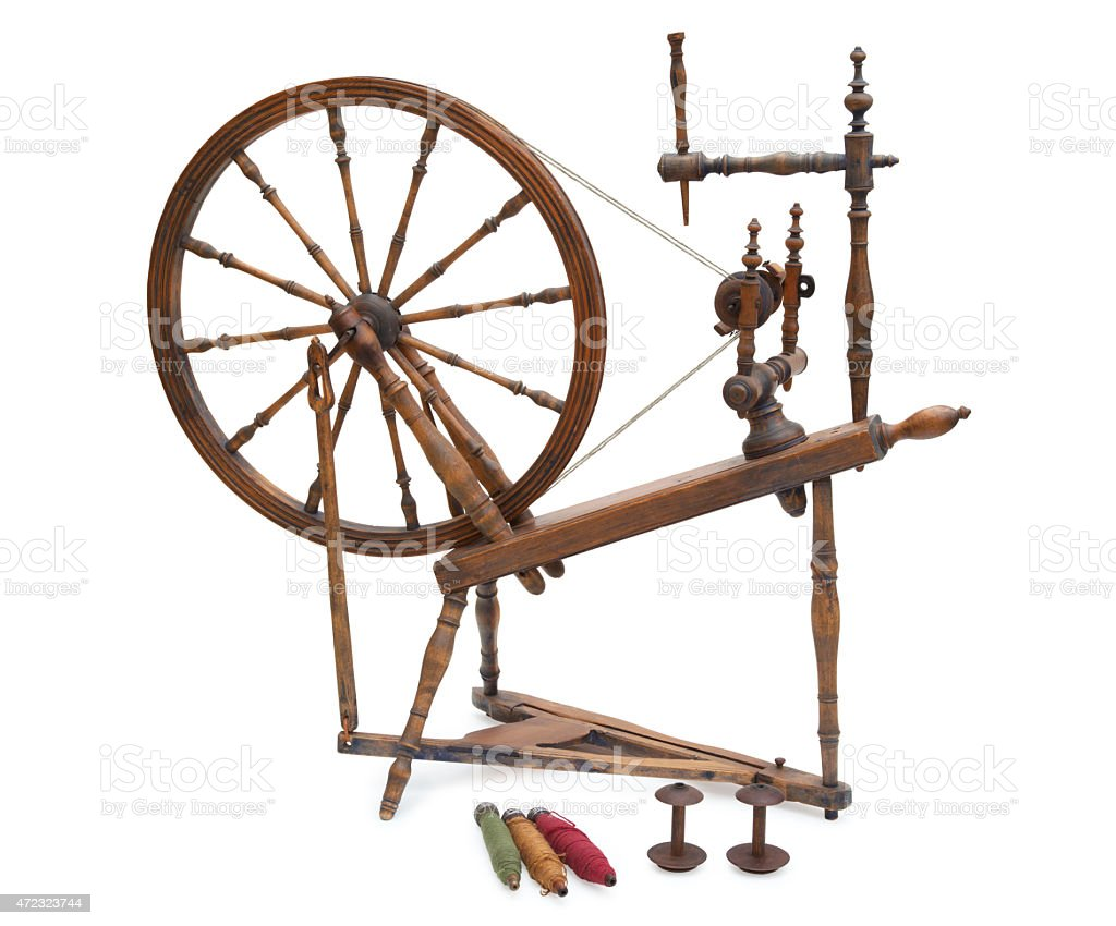 Antique spinning wheel with yarn and bobbins isolated on white stock photo