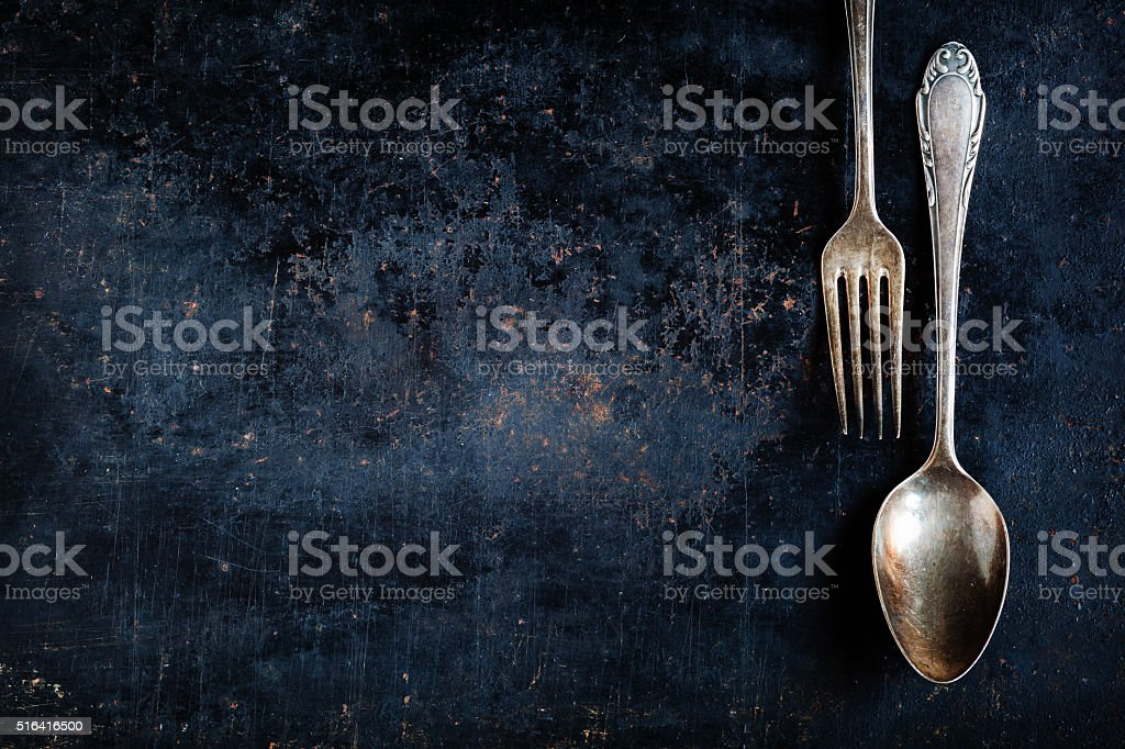 antique spoon and fork on a black baking sheet stock photo