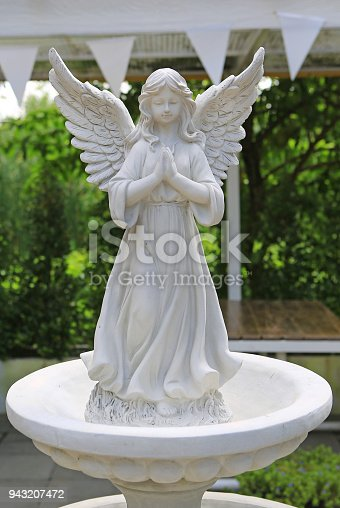 istock Antique statue of a winged angel with praying in the garden. 943207472