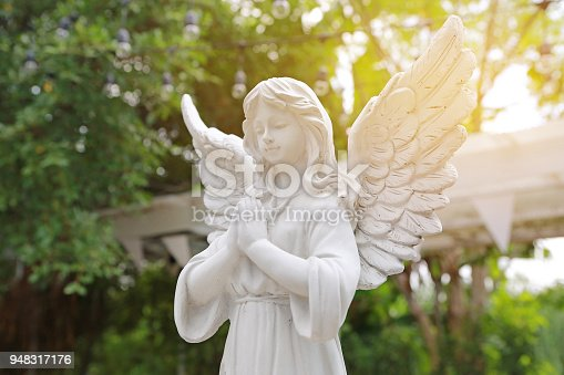 istock Antique statue of a winged angel with praying in the garden with rays of sunlight. 948317176