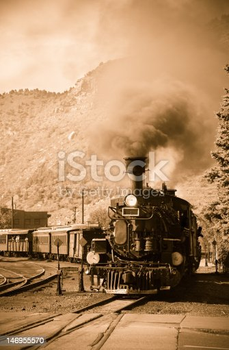 Sepia image of an antique steam locomotive in the American West.