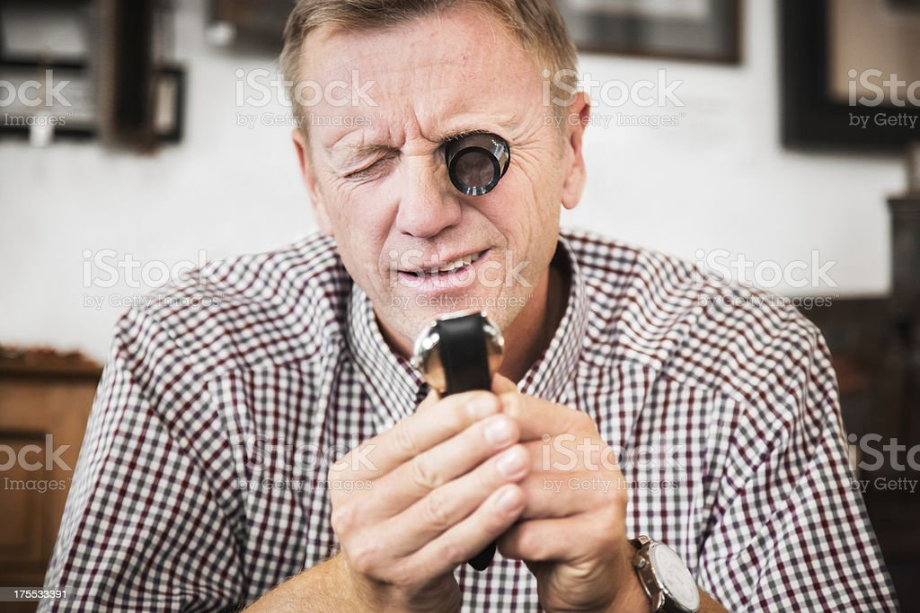 Antique Store Owner Examining Watch stock photo