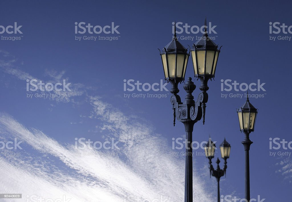 Antique streetlamps in front of blue sky royalty-free stock photo