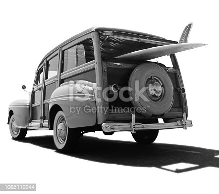 This is a black-and-white photo of an old retro Woody car with a surfboard sticking out of it isolated on a white background. There is a clipping paths included with this file.
