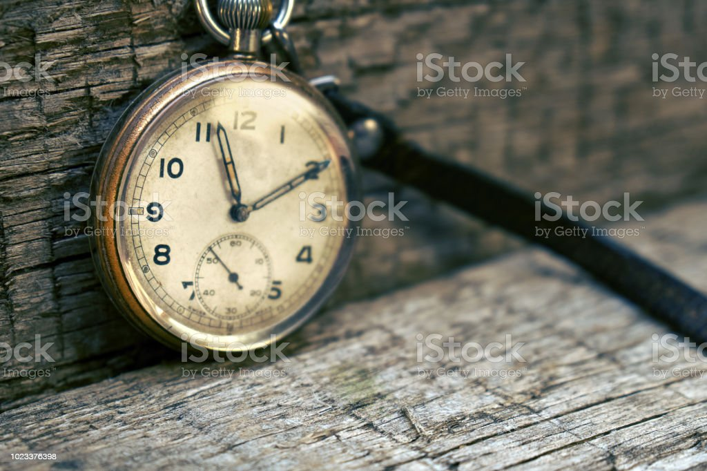 Vintage grandfather\'s swiss pocket watch on the wooden boards with a...