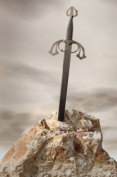 Antique sword stuck in stone rock stock photo