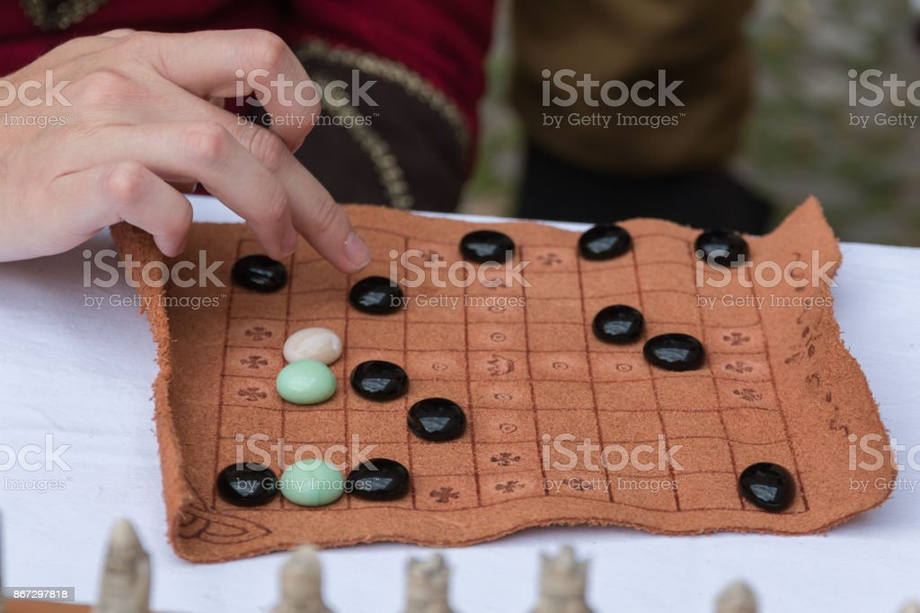 Antique Table Game with Oval Pieces and Brown Fabric Board stock photo