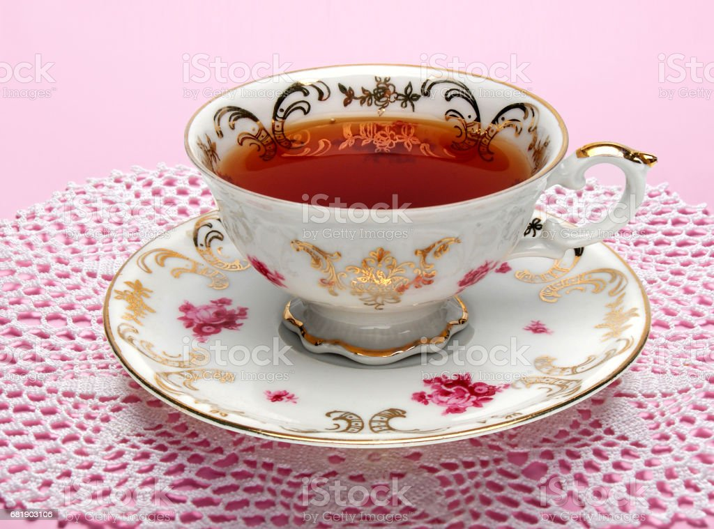 Antique tea cup full of tea on table stock photo