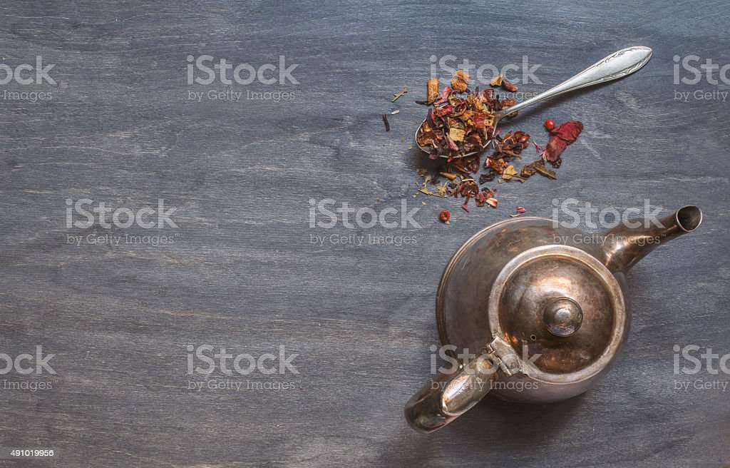 Antique teapot and strawberry tea on dark wooden background stock photo