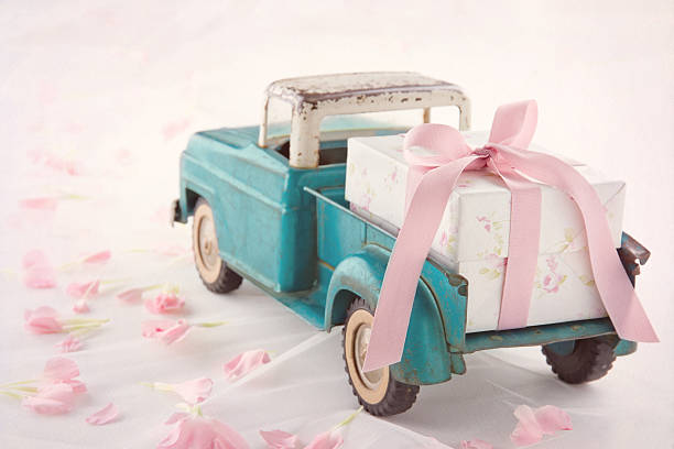 Antique toy truck carrying a gift box with pink ribbon stock photo