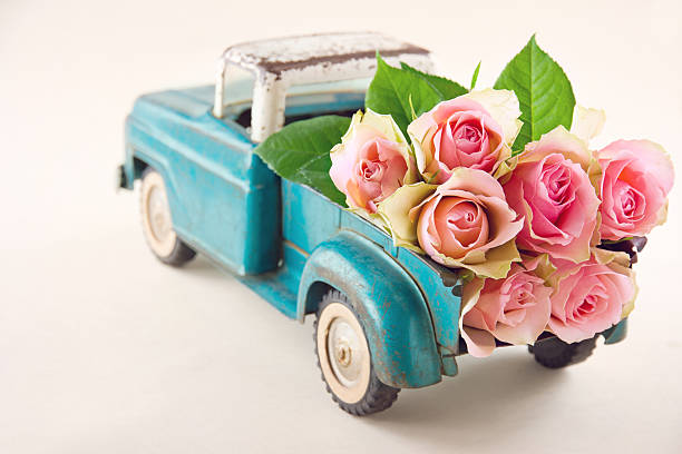 Antique toy truck carrying pink roses stock photo