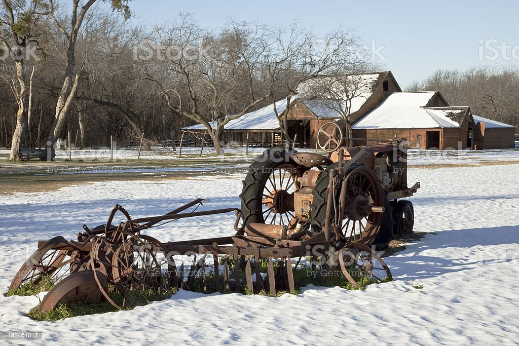 Antique Tractor and Disk Harrow in Snow- Covered Farmyard. royalty-free stock photo