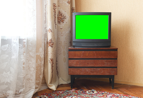 Antique TV with green screen on an antique wooden cabinet, old design in a house in the style of the 1980s and 1990s.Interior in the style of the USSR.