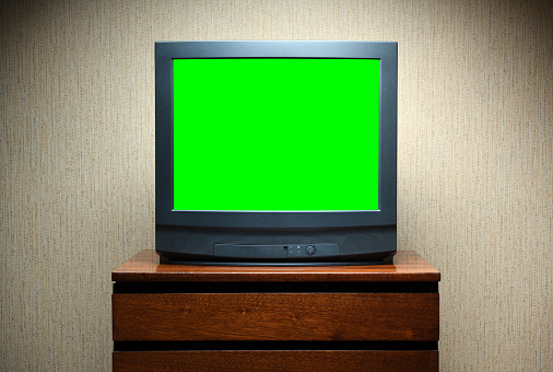 Antique TV with green screen on an antique wooden cabinet, old design in a house in the style of the 1980s and 1990s.