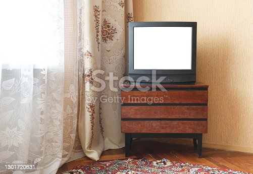 Antique TV with white screen on antique wooden cabinet, vintage design in 80s and 90s style house.