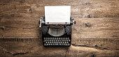istock Antique typewriter grungy textured paper wooden background 995786960