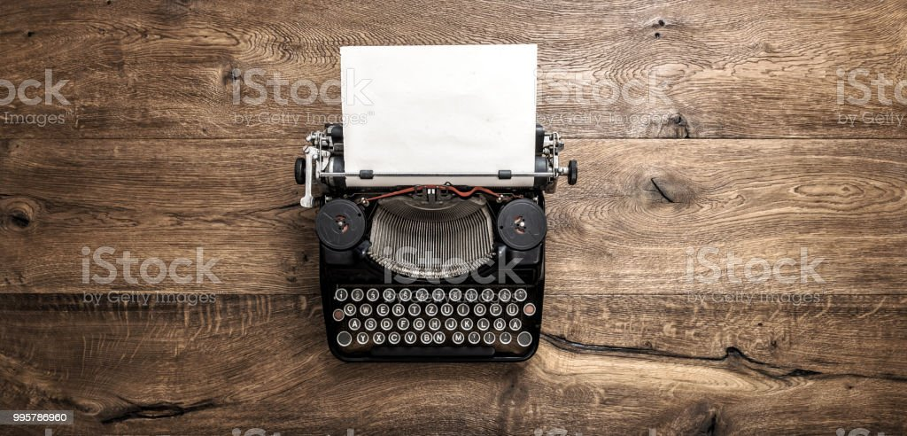 Antique typewriter grungy textured paper wooden background stock photo