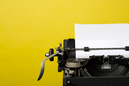 Close up shot of an antique typewriter with blank sheet of paper shot on a yellow background.
