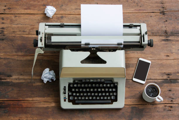 Antique typewriter with the Russian alphabet on an old table, mobile phone, cup of coffee stock photo