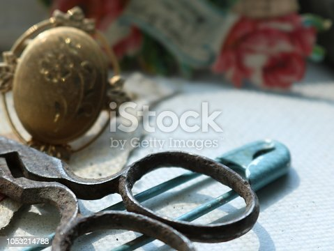 Vintage metal scissors displayed with gold brooch and blue baby safety pin