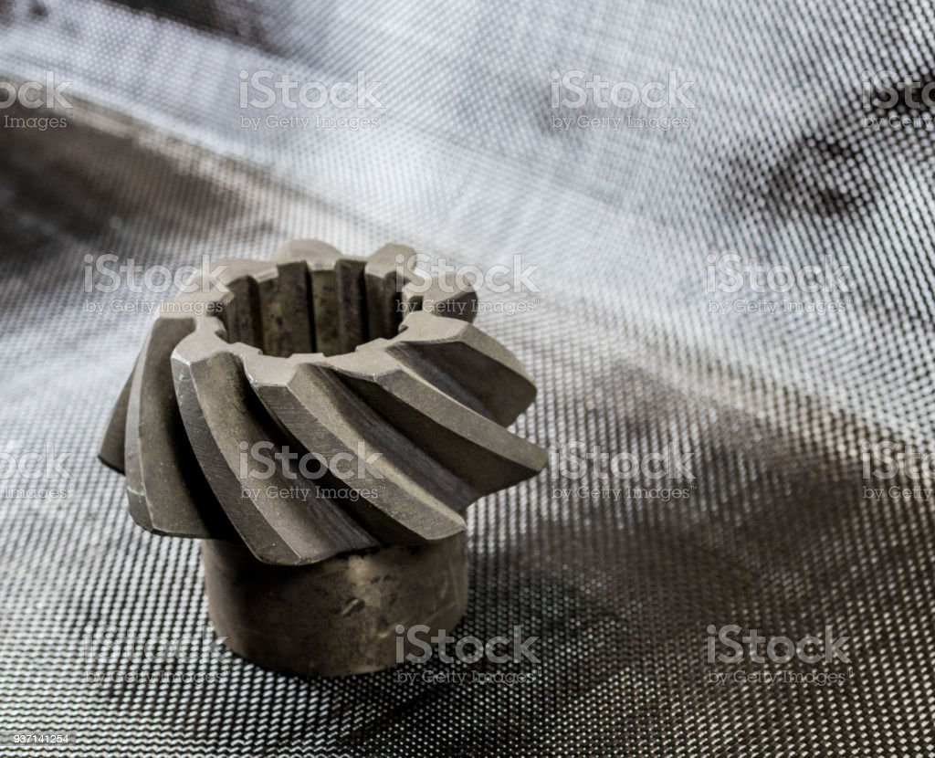 Antique vintage automotive pinion gear on plain weave carbon fiber stock photo