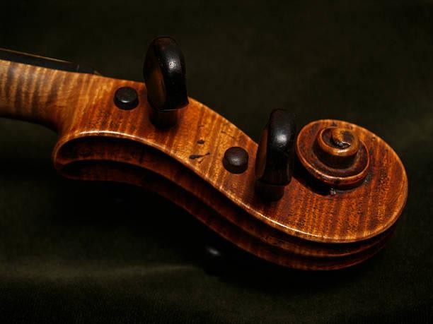 Antique Violin Scroll on Dark Green Velvet Background stock photo