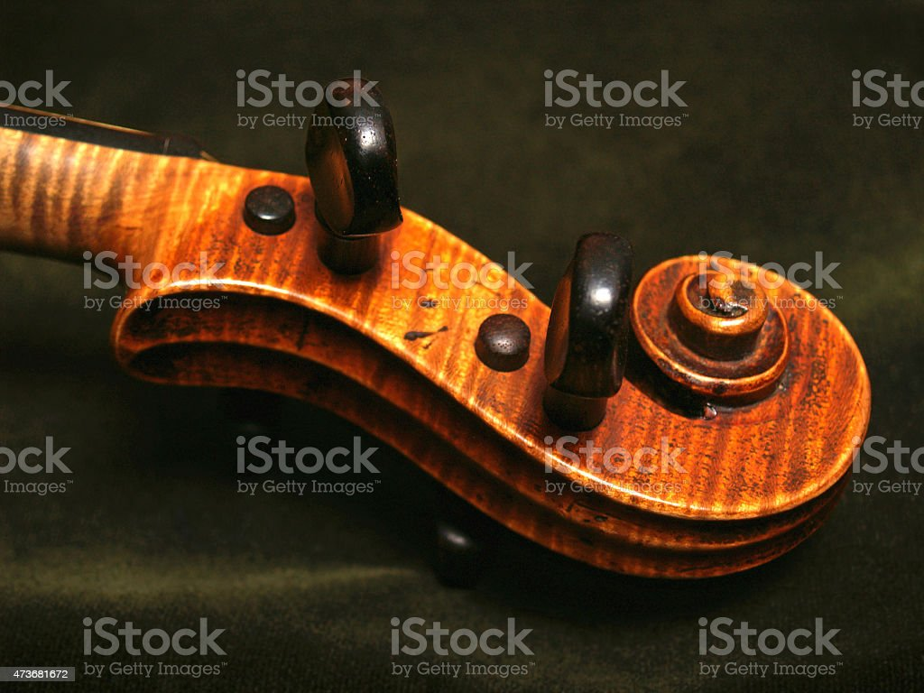 Antique Violin Scroll on Green Velvet Background stock photo
