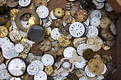 A box of antique watch faces at a Paris street vendors table.